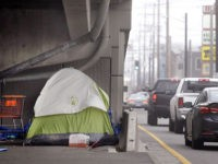A tent sits under an on-ramp as traffic drives past during morning rush hour in Seattle on Tuesday, Feb. 9, 2016. Even as homelessness declined slightly nationwide in 2015, it increased in urban areas, including Seattle, New York and Los Angeles. (AP Photo/Elaine Thompson)