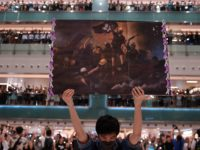 A man holds a poster as others gather at a shopping mall in the Shatin area of Hong Kong on September 11, 2019, to sing a recently penned protest song titled 'Glory to Hong Kong which has been gaining popularity in the city. (Photo by Nicolas ASFOURI / AFP) (Photo …