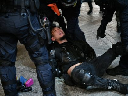 Police arrest a protester in the Causeway Bay area of Hong Kong on August 31, 2019, as people demonstrate, defying a ban on rallying -- and mounting threats from China -- to take to the streets for a 13th straight weekend. (Photo by Anthony WALLACE / AFP) (Photo credit should …
