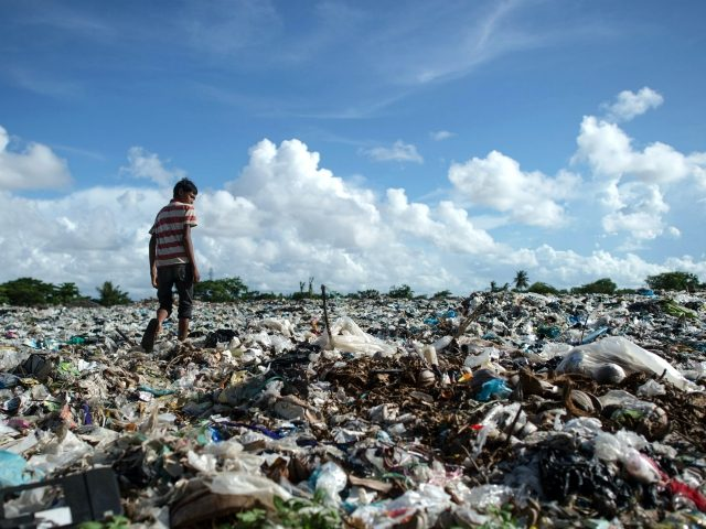 A boy walks at a garbage dump in Dala, on the outskirt of Yangon, on June 4, 2018. (Photo by Ye Aung THU / AFP) (Photo credit should read YE AUNG THU/AFP/Getty Images)
