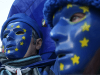 Pro-European Union, (EU), anti-Brexit demonstrators wear masks featuring the EU flag outside the Houses of Parliament in central London on December 18, 2017. / AFP PHOTO / Daniel LEAL-OLIVAS (Photo credit should read DANIEL LEAL-OLIVAS/AFP/Getty Images)