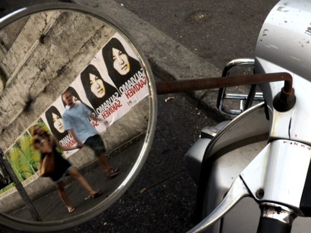 "eople walking by posters of Iranian Sakineh Mohammadi-Ashtiani which read ""save Sakineh"" are reflected in the mirror of a Vespa scooter parked on a street in central Rome on September 9, 2010. The 43-year-old woman was condemned to death by stoning in 2006 for adultery and complicity in her husband's …"