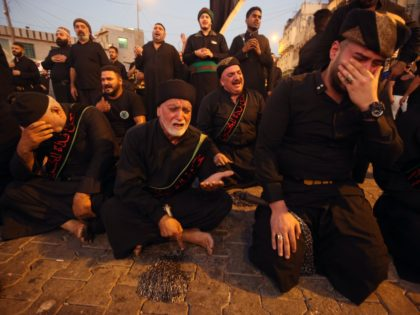 Iraqi Shiite Muslim men cry in the capital Baghdad's mostly Shiite neighbourhood of Kadhimiya on the eve of Ashura on September 9, 2019. - The religious commemoration of Ashura, which includes a ten-day mourning period starting on the first day of Muharram on the Islamic calendar, commemorates the seventh-century slaying …