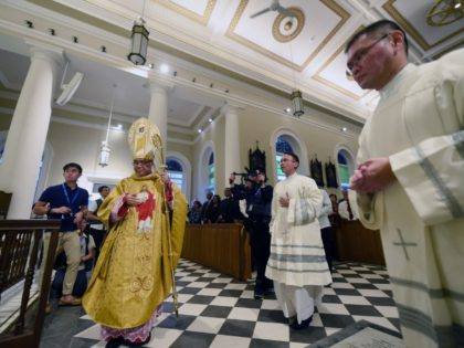 This photograph taken on February 14, 2017 shows Archbishop William Goh Seng Chye (L) walking to the altar during a mass at the Roman Catholic Cathedral of the Good Shepherd 120th anniversary in Singapore. Singapore's oldest Roman Catholic church was built by Father Jean-Marie Beurel in 1847 and underwent extensive …