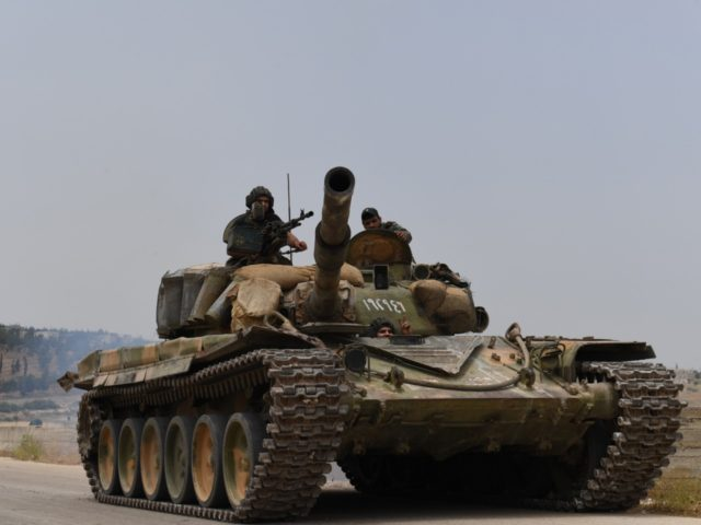 A tank belonging to the Syrian regime forces drives on a road leading to the town of Jalamah in Syria's Hama governorate during clashes with jihadists on June 8, 2019. - Last week, the jihadists and allied rebels launched a counterattack against regime forces in the northwest of Hama province, …