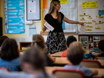 A teacher talks to her pupils in her classroom on the first day of the start of the school year, at the Chaptal elementary school in Paris, on September 2, 2019. - In France some 12.4 million students crossed the doors of elementary schools (6.7 million), secondary school (3.4 million) …