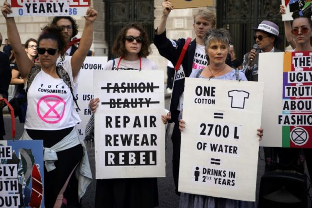 Extinction Rebellion argues that fast fashion is hugely wasteful hold up anti-fashion placards as they block a road on the third day of London Fashion Week in London on September 15, 2019.