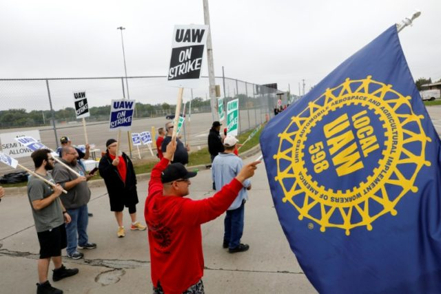 Striking members of the United Auto Workers (UAW) wave flags and banners at the General Motors plant in Flint, Michigan