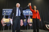 FILE - In this April 22, 2016 file photo, former Democratic presidential candidate Sen. Bernie Sanders, I-Vt., holds hands with Rep. Tulsi Gabbard, D-Hawaii, during a town hall at Gettysburg College, in Gettysburg, Pa. Gabbard, a Democratic congresswoman, is eyeing a White House run. The Iraq war veteran has visited …