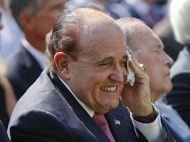 Rudy Giuliani, an attorney for President Donald Trump, center, wipes his forehead as he listens to President Donald Trump speak before Trump signed H.R. 1327, an act ensuring that a victims' compensation fund related to the Sept. 11 attacks never runs out of money, in the Rose Garden of the …
