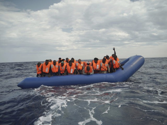 A migrant waves his hand in the air from on a blue rubber boat some 14 nautical miles from the coast of Libya in Mediterranean Sea, Sunday, Sept. 8, 2019. Humanitarian groups SOS Mediterranee and Doctors Without Borders have successfully rescued 50 migrants and brought them aboard the Ocean Viking. …