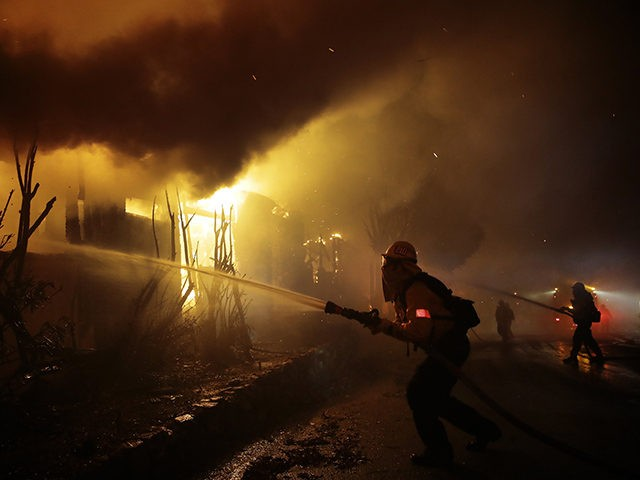 Firefighters try to hose down flames as homes burn in the Getty fire area along Tigertail Road, Monday, Oct. 28, 2019, in Los Angeles. (AP Photo/Marcio Jose Sanchez)