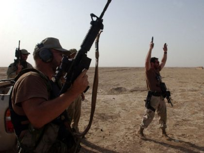 "KUNDUZ, NORTHERN AFGHANISTAN - AUGUST 26: U.S. Army Special Forces soldier nicknamed ""Mike"" (R) raises his arms in celebration after gunning down a target with his side arm while on a target range near the town of Kunduz August 26, 2002 in Northern Afghanistan. U.S. Special Forces have recently begun …"