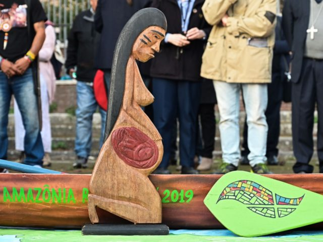 A wooden carved sculpture of a pregnant woman and a pirogue's model, symbolizing the stakes within the only way to travel on the Amazon rivers, is pictured during a procession of indigenous leaders, prelates and people participating in the Special Assembly of the Synod of Bishops for the Pan-Amazon Region, …