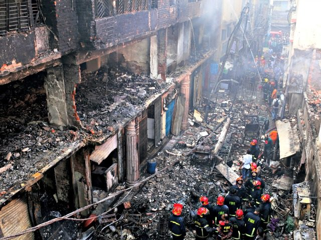 In this, Thursday, Feb. 21, 2019 file photo, locals and firefighters gather around buildings that caught fire late Wednesday, Feb. 20 in Dhaka, Bangladesh. After more than 1,100 people died when a garment factory complex collapsed in Dhaka, Bangladesh authorities imposed more stringent safety rules. But corruption and lax enforcement …