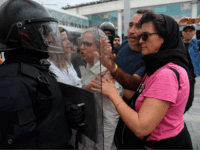 TOPSHOT - Protesters clash with a Spanish policeman outside El Prat airport in Barcelona on October 14, 2019 as thousands of angry protesters took to the streets after Spain's Supreme Court sentenced nine Catalan separatist leaders to between nine and 13 years in jail for sedition over the failed 2017 …