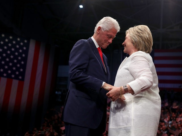 Democratic presidential candidate former Secretary of State Hillary Clinton (R) and her husband former U.S. president Bill Clinton embrace during a primary night event on June 7, 2016 in Brooklyn, New York. Hillary Clinton surpassed the number of delegates needed to become the democratic nominee over rival Bernie Sanders with …