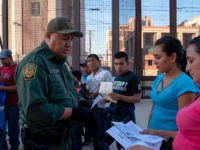 US Customs and Border Protection agent checks documents of a small group of migrants, who crossed the Rio Grande from Juarez, Mexico, on May 16, 2019, in El Paso, Texas. - About 1,100 migrants from Central America and other countries are crossing into the El Paso border sector each day. …