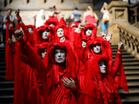 "TOPSHOT - Extinction Rebellion climate change activists in red costume attend a mass ""die in"" in the main hall of the Natural History Museum in London on April 22, 2019, on the eighth day of the environmental group's protest calling for political change to combat climate change. - Climate change …"