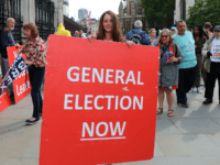 Protestors hold placards near the Houses of Parliament in central London on September 5, 2019. - UK Prime Minister Boris Johnson called Thursday for an early election after a flurry of parliamentary votes tore up his hardline Brexit strategy and left him without a majority. (Photo by ISABEL INFANTES / …