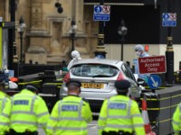 LONDON, ENGLAND - AUGUST 14: A general view of Police officers searching the scene as forensic officers work on the vehicle that crashed into security barriers, injuring a number of pedestrians early this morning, outside the Houses of Parliament on August 14, 2018 in London, England. A man has been …