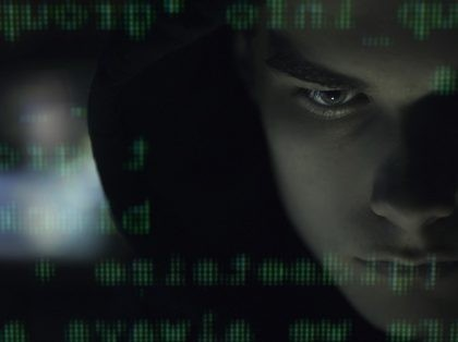 Cool young hacker with hoodie posing in the dark and programming code, cyber security and development concept