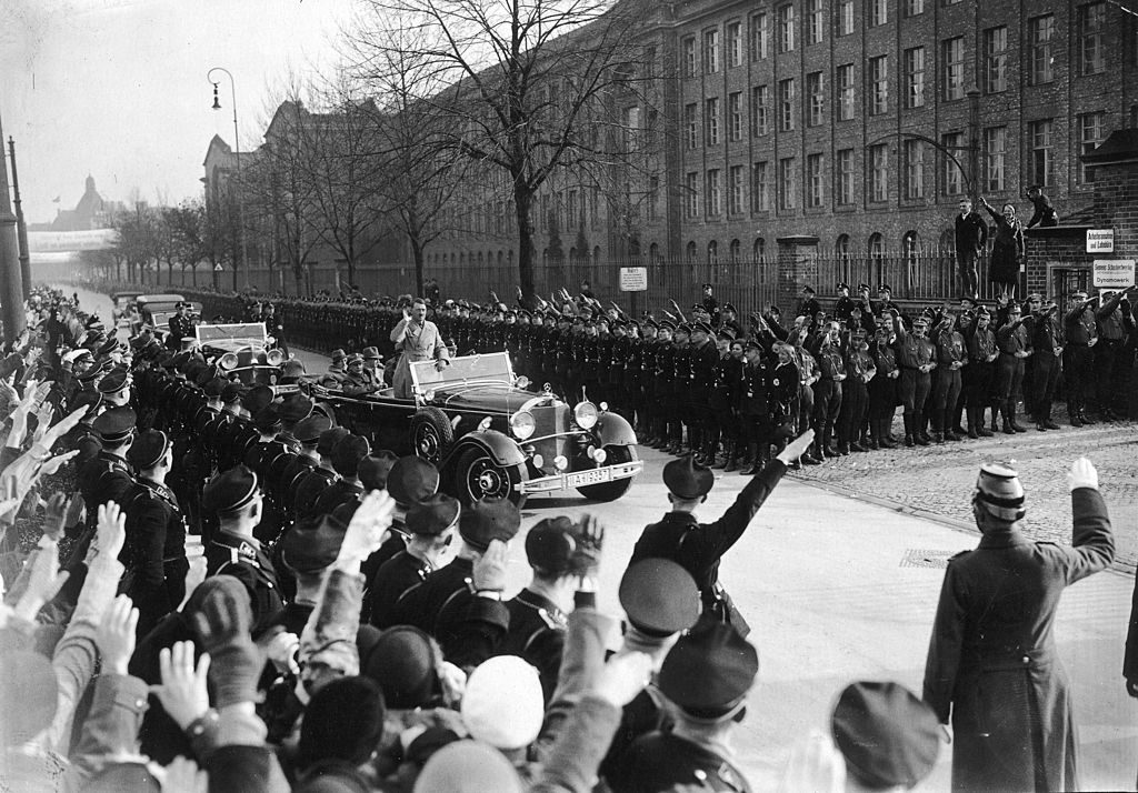 Nazi leader Adolf Hitler (1889 - 1945) is greeted by crowds outside the Siemens-Schuckertwerke factory in Berlin, 10th November 1933. Hitler's speech at the factory, part of his campaign for the 12th November Reichstag election, was broadcast on German national radio. (Photo by FPG/Archive Photos/Getty Images)
