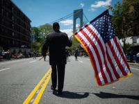 A veteran carries an American flag as he marches on the street May 27, 2019 during the 152nd Memorial Day Parade in the New York City borough of Brooklyn. - The Kings County Parade is one of the oldest Memorial Day Parades in the nation. (Photo by Johannes EISELE / …