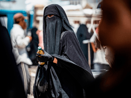 A woman wearing a niqab (full face veil) holds a bottle of sunflower oil distributed as part of food aid at al-Hol camp for displaced people in al-Hasakeh governorate in northeastern Syria on July 22, 2019, as people collect UN-provided humanitarian aid packages. (Photo by Delil souleiman / AFP) (Photo …