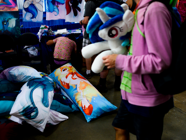 "An attendee walks past a vendor selling pillows during the BronyCon convention, a gathering for ""My Little Pony"" fans, at the Baltimore Convention centre in Baltimore, Maryland on August 1, 2019. - BronyCon is an annual fan convention held for fans of ""My Little Pony: Friendship Is Magic,"" among them …"