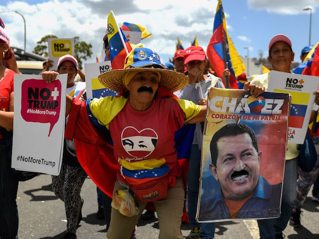 A supporter of the Venezuelan government displays a poster of late President Hugo Chavez during a rally against US sanctions in Caracas on August 10, 2019. - Earlier this week, US President Donald Trump ordered a freeze on all Venezuelan government assets in the United States and barred transactions with its authorities, in Washington's latest move against President Nicolas Maduro. (Photo by Federico PARRA / AFP) (Photo credit should read FEDERICO PARRA/AFP/Getty Images)
