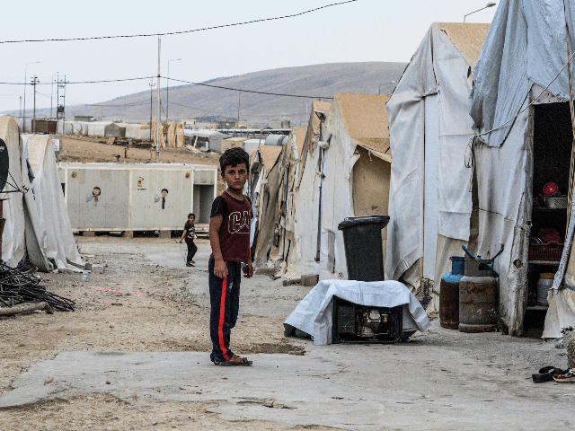 A boy stands in an alley between tents at a camp for internally displaced persons (IDP) of Iraq's Yazidi minority in the Sharya area, some 15 kilometres from the northern city of Dohuk in the autonomous Iraqi Kurdistan region on August 30, 2019. (Photo by Zaid AL-OBEIDI / AFP) (Photo …