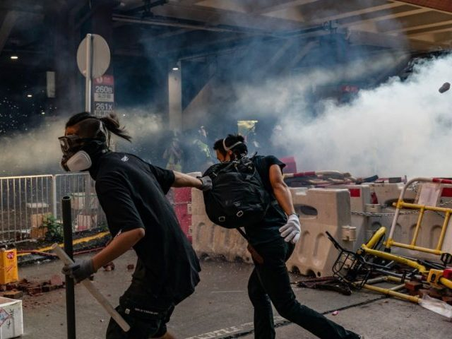 HONG KONG, CHINA - SEPTEMBER 21: Pro-democracy protesters run after police fired tear gas at them during a clash after an anti-government rally in Tuen Mun district on September 21, 2019 in Hong Kong, China. Pro-democracy protesters have continued demonstrations across Hong Kong, calling for the city's Chief Executive Carrie …