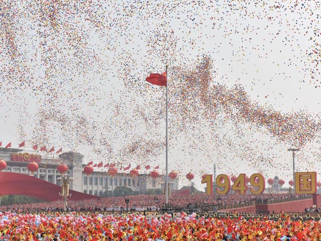 TOPSHOT - Balloons fly past the national flag at the end of a military parade at Tiananmen Square in Beijing on October 1, 2019, to mark the 70th anniversary of the founding of the People's Republic of China. (Photo by GREG BAKER / AFP) (Photo credit should read GREG BAKER/AFP/Getty Images)