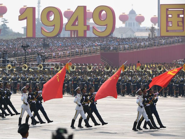 Chinese soldiers march with the national flag (C), flanked by the flags of the Communist Party of China (R) and the People's Liberation Army (L) during a military parade at Tiananmen Square in Beijing on October 1, 2019, to mark the 70th anniversary of the founding of the People's Republic of China. (Photo by GREG BAKER / AFP) (Photo credit should read GREG BAKER/AFP/Getty Images)