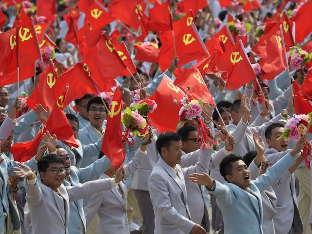 People wave Communist Party flags during a military parade in Tiananmen Square in Beijing on October 1, 2019, to mark the 70th anniversary of the founding of the People's Republic of China. (Photo by GREG BAKER / AFP) (Photo credit should read GREG BAKER/AFP/Getty Images)