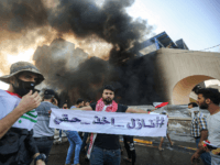 "A protester holds up a banner reading in Arabic ""#ComingForMyRights as he stands with others before a burning building amdist clashes with Iraqi riot police during a demonstration against state corruption and poor services, between the capital Baghdad's Tahrir Square and the high-security Green Zone district, on October 1, 2019. …"