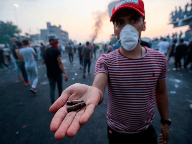 An Iraqi protester displays bullet casings during a demonstration against state corruption, failing public services and unemployment at Tayaran square in Baghdad on October 2, 2019. - Iraq's president and the United Nations urged security forces to show restraint after two protesters were killed in clashes with police that other …