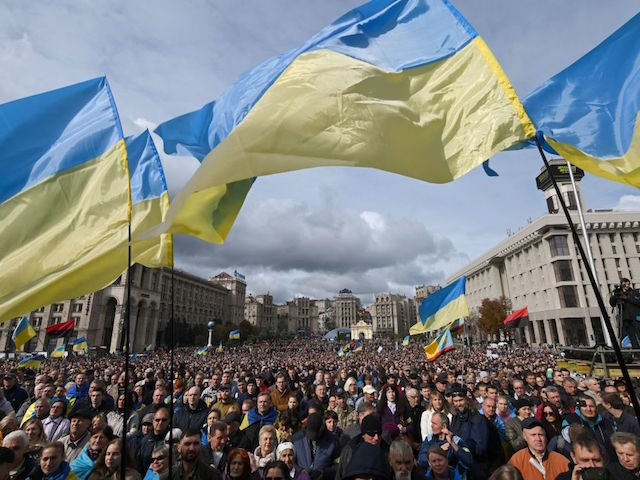 "Demonstrators wave Ukraine national flags as they gather in central Kiev on October 6, 2019 to protest broader autonomy for separatist territories, part of a plan to end a war with Russian-backed fighters. - Protesters chanted ""No to surrender!"", with some holding placards critical of President Volodymyr Zelensky in the …"