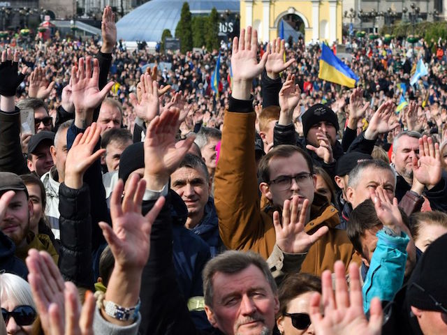 "Demonstrators raise their hands as they gather in central Kiev on October 6, 2019 to protest broader autonomy for separatist territories, part of a plan to end a war with Russian-backed fighters. - Protesters chanted ""No to surrender!"", with some holding placards critical of President Volodymyr Zelensky in the crowd, which police said had swelled to around 10,000 people. Ukrainian, Russian and separatist negotiators agreed on a roadmap that envisages special status for separatist territories if they conduct free and fair elections under the Ukrainian constitution. (Photo by Genya SAVILOV / AFP) (Photo by GENYA SAVILOV/AFP via Getty Images)"