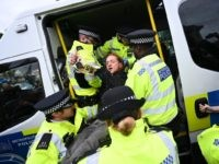 A climate change activist from the Extinction Rebellion group is arrested by police in Trafalgar Square in central London, on October 7, 2019 during the group's global climate protests. - Extinction Rebellion has scheduled non-violent protests chiefly in Europe, North America and Australia over the next fortnight. (Photo by Ben …