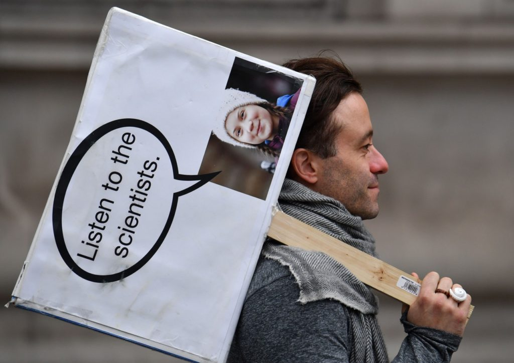 """An activist carries a placard with an image of Greta Thunberg as he protests on Whitehall, by Downing Street during the second day of climate change demonstrations by the Extinction Rebellion group in central London, on October 8, 2019. - Climate protesters from Sydney to New York blocked roads Monday, sparking hundreds of arrests, as two weeks of civil disobedience demanding immediate action to save the Earth from """"extinction"""" kicked off. The demonstrations, triggered by the group Extinction Rebellion, were mostly limited to a few hundred people in each city, far from the size of last month's massive Greta Thunberg-inspired protests. (Photo by Ben STANSALL / AFP) (Photo by BEN STANSALL/AFP via Getty Images)"""