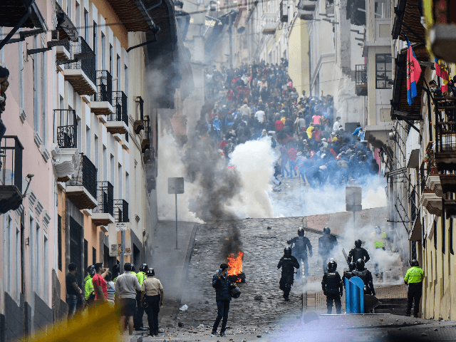 Riot police confront demonstrators during clashes in Quito as thousands march against Ecuadorean President Lenin Moreno's decision to slash fuel subsidies, on October 9, 2019. - Unions and other groups alongside thousands of farmers and indigenous people are expected in the streets of the capital Quito. Protests and clashes erupted …