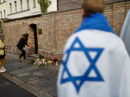 People lays flowers on October 10, 2019 at the synagogue in Halle, eastern Germany, one day after the attack where two people were shot dead. - At least two people were shot dead in Halle on October 9, 2019, with witnesses saying a synagogue was among the gunmen's targets as …