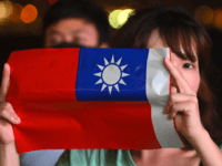 A woman holds a Taiwanese flag as she joins others at a rally to mark Taiwan's National Day, in the Tsim Sha Tsui district in Hong Kong on October 10, 2019. - Taiwan's National Day, also called called Double-Ten in a reference to the nationalist Republic of China set up …