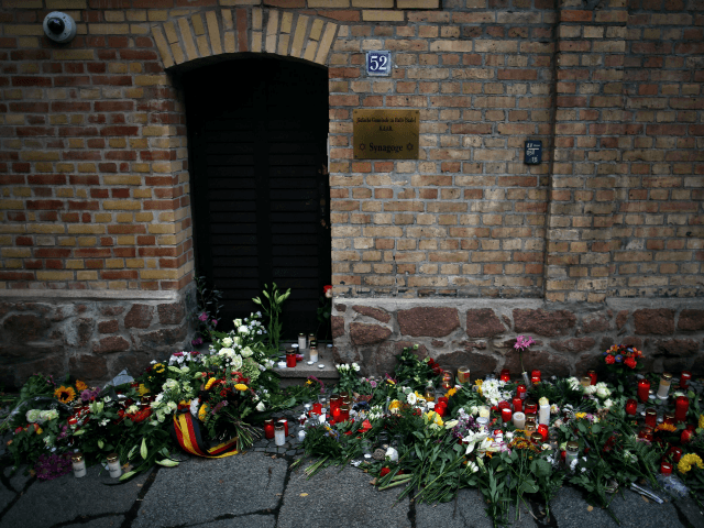Candles and flowers are seen at a makeshift memorial in front of the synagogue in Halle, eastern Germany, on October 10, 2019, one day after the attack where two people were shot dead. - German leaders visited the scene of the deadly anti-Semitic gun attack carried out on the holy …