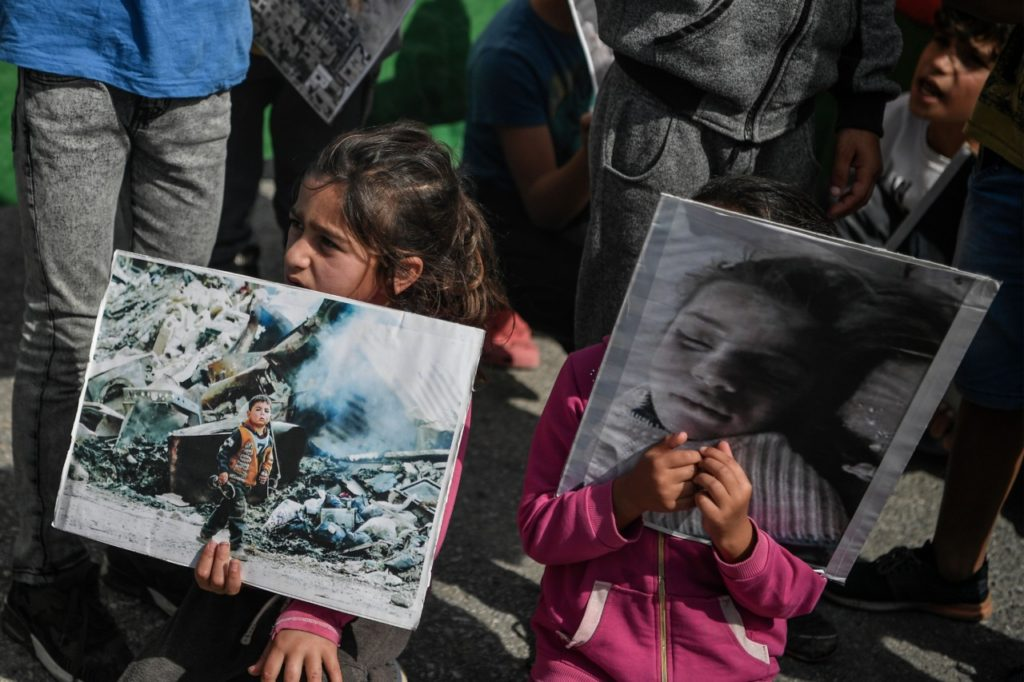 Children hold photographs, as Syrian Kurd refugees protest at the Ritsona camp, some 80 km north of Athens, on October 10, 2019, after Turkey launched an assault on Kurdish forces in northern Syria with air strikes and explosions reported along the border. - Ritsona camp houses some 950 refugees, mainly Syrians and Kurds (Photo by LOUISA GOULIAMAKI / AFP) (Photo by LOUISA GOULIAMAKI/AFP via Getty Images)