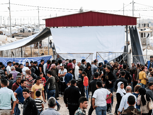 Syrian refugees fleeing the Turkish incursion in Northern Syria wait to receive aid from the UNHCR, local Kurdish non-profit, BCF (Barzani Charity Foundation) and other International NGOs as more than 200 arrive at the facility on October 17, 2019 in Dohuk, Iraq. More than 1000 refugees have arrived in Northern …