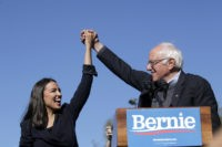 NEW YORK, NY - OCTOBER 19: Democratic presidential candidate, Sen. Bernie Sanders (D-VT) holds hands with Rep. Alexandria Ocasio-Cortez (D-NY) during his speech at a campaign rally in Queensbridge Park on October 19, 2019 in the Queens borough of New York City. This is Sanders' first rally since he paused …