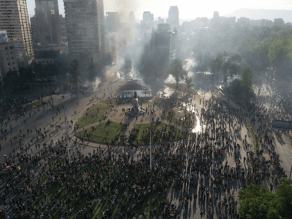 In this aerial view demonstrators clash with riot police at Plaza Italia square on October 21, 2019, for a fourth straight day as part of protests against a now suspended hike in metro ticket prices. - Chile ordered an overnight curfew for the third day in a row on Monday …